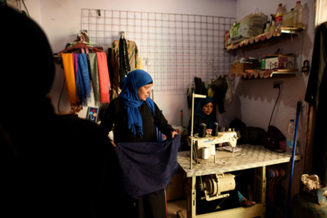 Rasha and her two other sisters in their clothing shop. The three sisters cooperated to support themselves financially in order to create a better life for their daughters and protect them from their previous faith.
