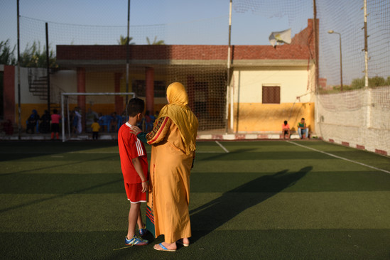 """Mona – a former """"child bride"""" escorts her son on the soccer field. She's been financially independent for the past five years. Working as a butter maker from her home to provide for her young son and older daughters."""
