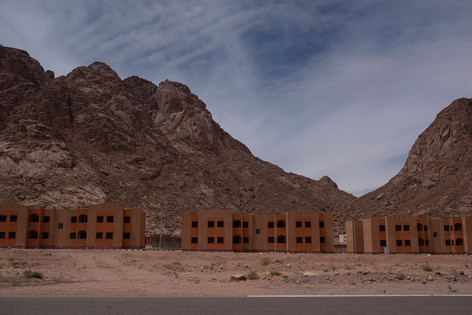 Concrete apartment buildings stand empty across between mountains in St. Catherine, South Sinai, Egypt; a protected mountainous area inhabited by native Bedouin communities. In disregard to environmental laws and Bedouin culture the blocks were built by the government as housing services for the Bedouin locals and workers coming from across the country. Nevertheless, nature and tradition remains to dominate the space.  These buildings represent the long standing power struggle and tension between the government and the local Bedouin community. Connected to the land by blood, the Bedouin community's knowledge of the mountains and movements within it intimidates a government that seeks control and sole power.