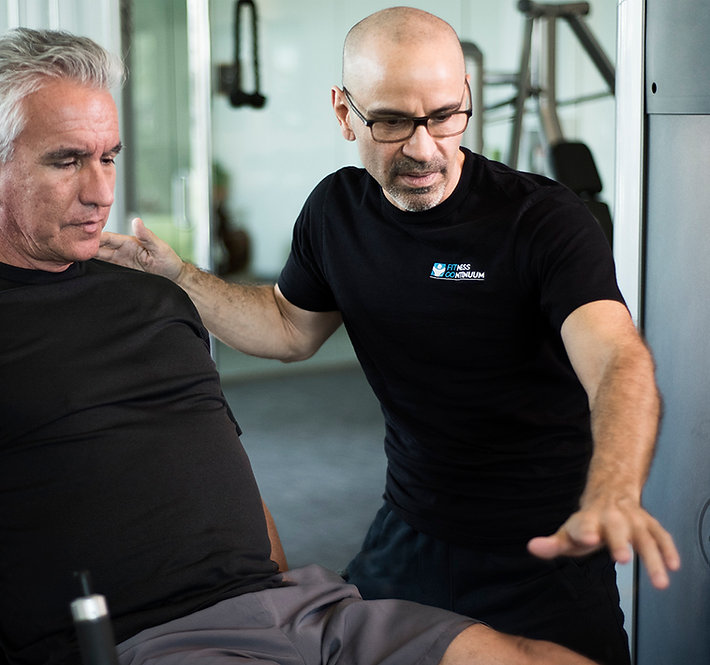Eduardo Chacon Medical Fitness Trainer supervising patient performing on leg extnsion machine