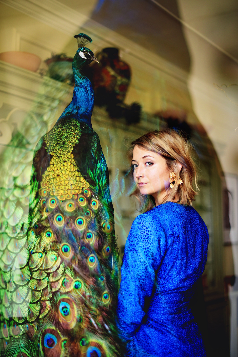 Artist Lily Adele posing with a giant taxidermy peacock