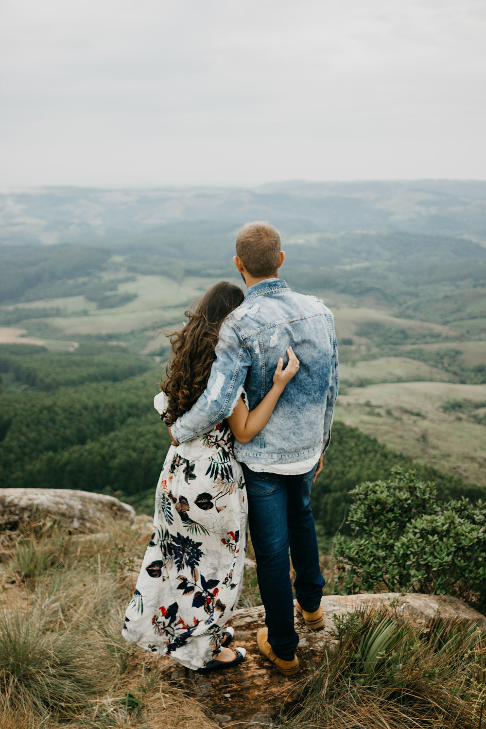 couple on top of hill overlooking valley