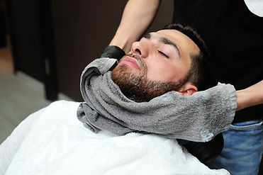 Barber preparing man face for shaving wi