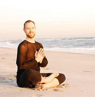 Seated meditation with anjali mudra by the beach