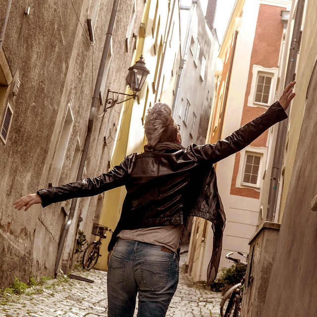 Woman with an almost mohawk walking through narrow cobblestoned streets Photo by TodayVienna