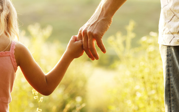 a parent holds the hand of a small child