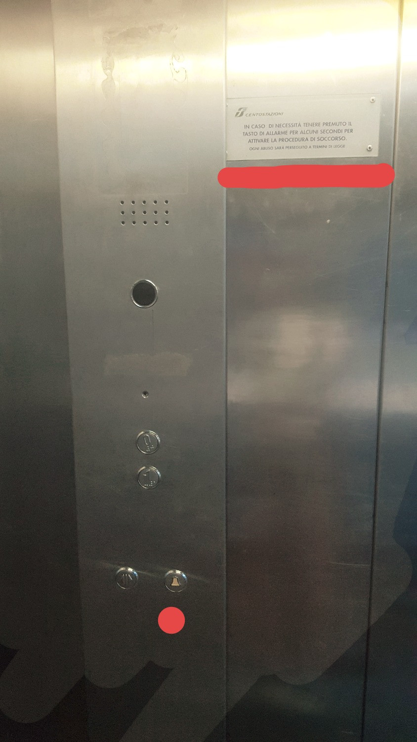 An elevator's emergency button and instructions are placed far from each other