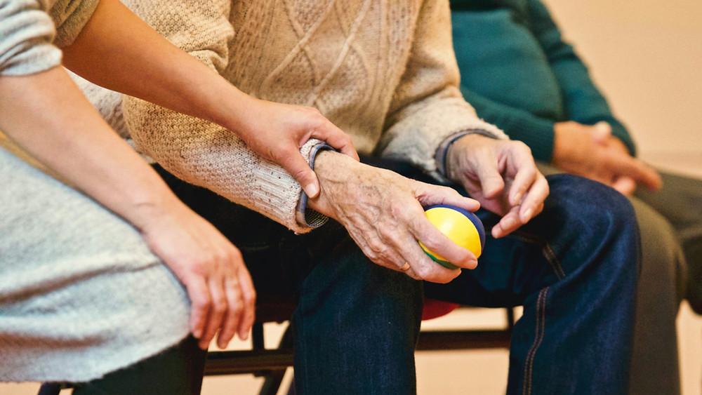 Altenpfleger mit Mann hält Hand