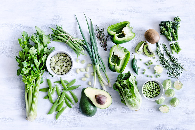 Layout of green vegetables arranfed on a stone table: celery, soybeans, string beans, green peppers, scallions, snap peas, avocado, romaine lettuce, broccolini, serrano peppers, kiwi, peas, brussel sprouts, rosemary and thyme.