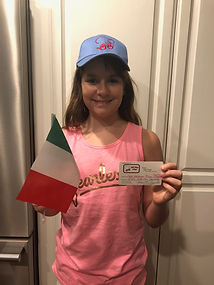 A young girl holding an Italian flag and wearing a Chi-Chi's hat