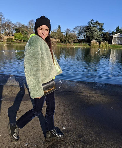 Terri looking at the camera smiling in-front of the pond at Gunnersbury park