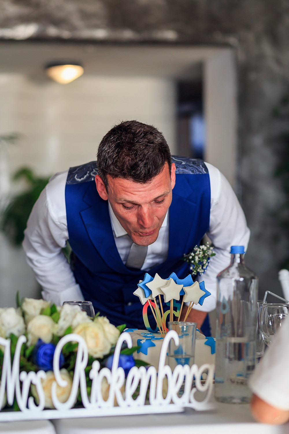 Groom blowing out candles