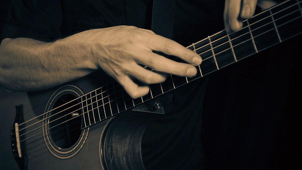 Photo gros plan sur les main du guitariste qui joue en tapping sur une guitare acoustique Pellerin Grand Auditorium Concert.