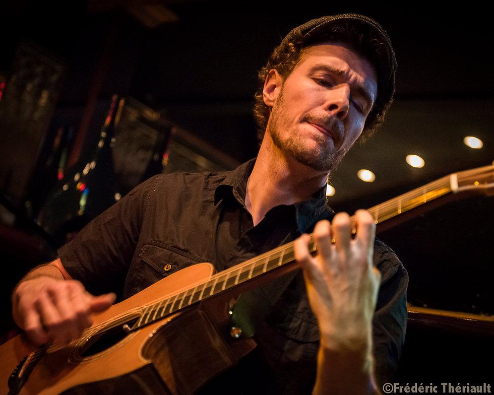 Photo du lancement de l'album L'Antre de François Pelletier. On y voit le guitariste fingerstyle en action dans un décors urbain.