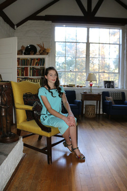 in a blue dress on a yellow chair