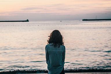 Ragazza che guarda l'orizzonte per ritrovare se stessa ha bisogno di andare dello psicologo