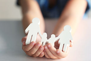 Child holding figure in shape of happy family, closeup. Adoption concept.jpg