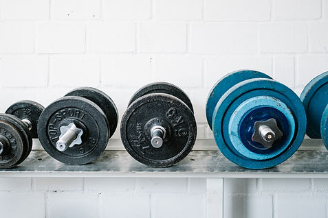 A number of dumbbells lined up in a gym. This image heads the Hungry4Fitness Training Equipment page. This page contains loads of blogs on the best training equipment on the market.
