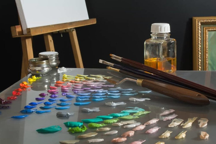 Artists-studio-workspace-showing-palette-with-premixed-oil-paint-colors-in-shades-and-nuances-arrang