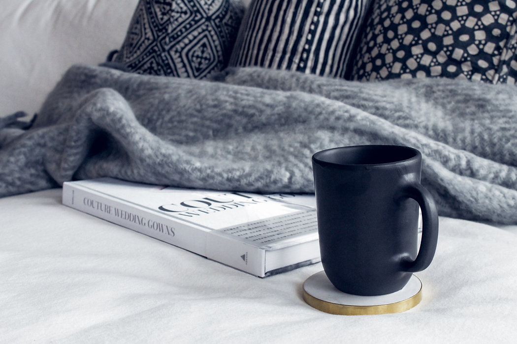 black-ceramic-mug-on-round-white-and-bei