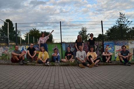 Gruppenbild der 12 Mitglieder des Vereins. Sie sitzen im mittleren Teil des Bildes auf einem Stück Wiese auf dem Boden vor einer kleinen bemalten Mauer. Dahinter ein größerer Zaun zum angrenzenden Basketballplatz. Im unterem Bildabschnitt befindet sich der Gehweg.