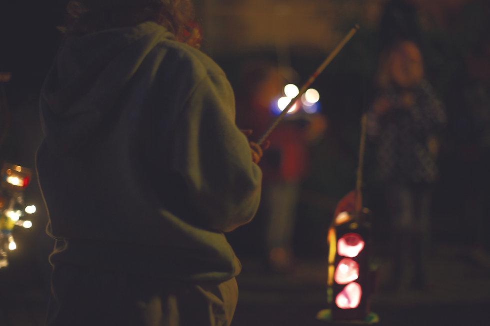 Person von hinten mit Lampion in der Hand