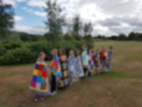 The children showing off the beautiful blankets from Patchwork Garden