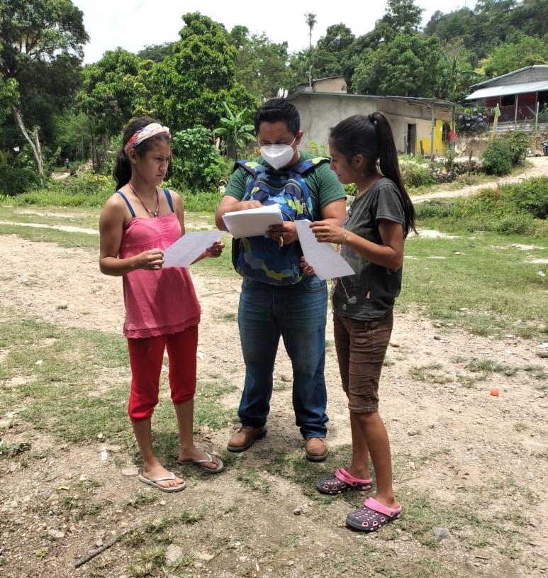 A facilitator at the Centro de San Nicolas satellite school in Copan checking the work of two students.