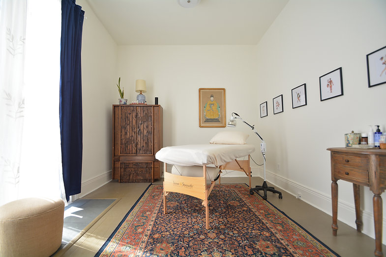 A treatment room at Hidden Root Acupuncture featuring a treatment table, TDP lamp, bright window, and Chinese art work
