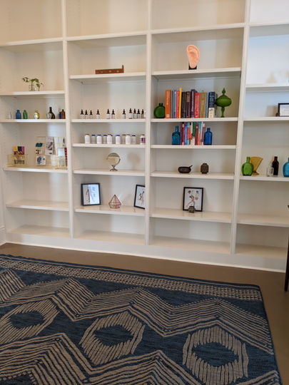 A bookshelf of herbs and herbal formulas, tinctures, books, and trinkets at Hidden Root Acupuncture
