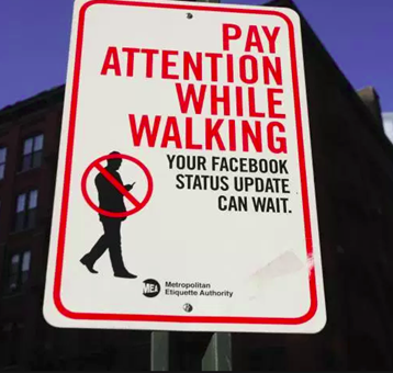 Street sign reminding pedestrians not to text and walk.
