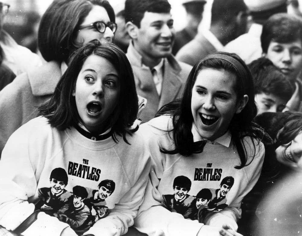 Young fans eagerly await the arrival of The Beatles.