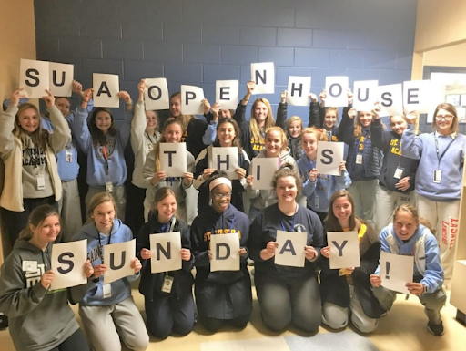 Current SUA students showing their spirit by holding up signs for Open House on Sunday for students looking for high schools.