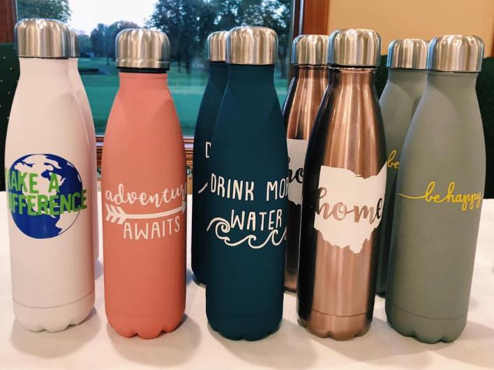 @Monogramsbymaya displayed on objects like water bottles.