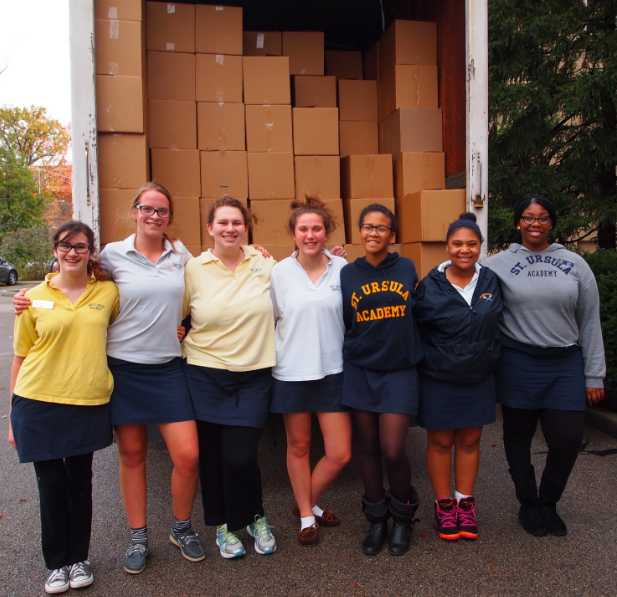 Participants in a past SUA food drive happily pose for a photo in front of a full truck.