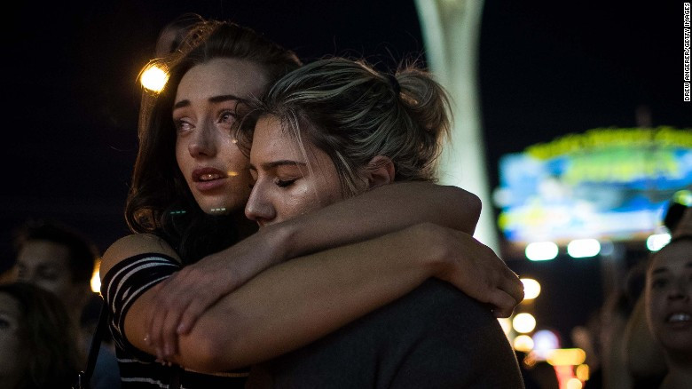 Two friends demonstrate the nation's mourning as they embrace during a candlelight vigil for victims of the shooting.