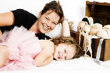 Mother of toddler ballet girl lying on t