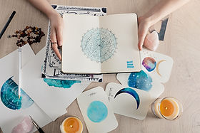 Top view of astrologer holding notebook with watercolor drawings and zodiac signs on cards