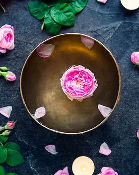Tibetan singing bowl with floating rose inside. Burning candles, tea rose flowers and peta