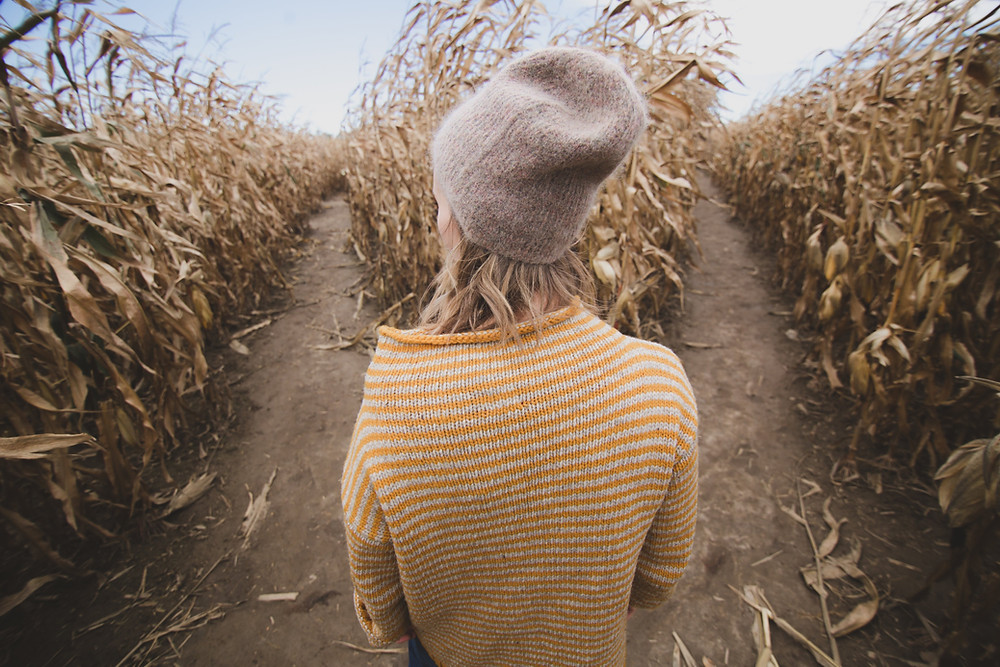 Girl with a hat standing between two walkways in a crop field