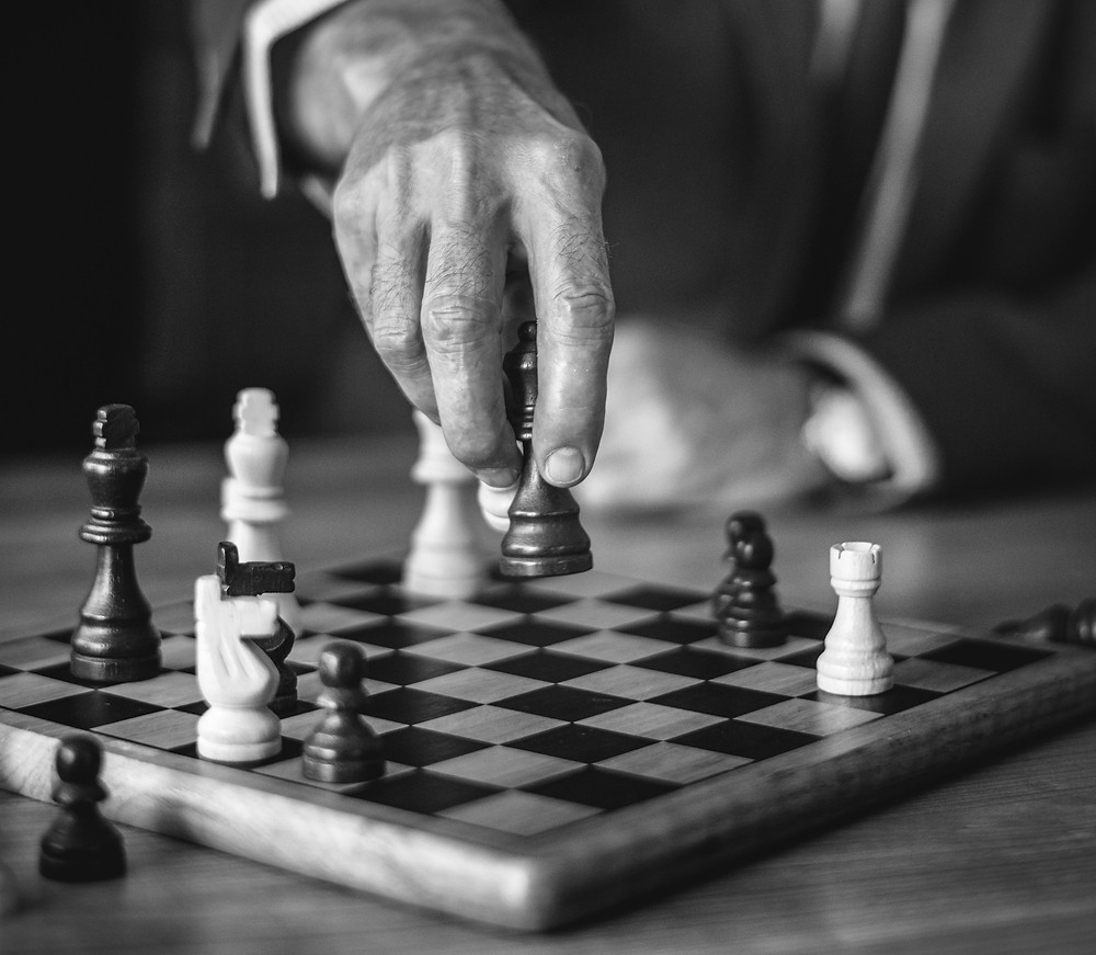 man hand playing chess black white