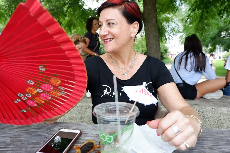 woman holding red hand-held fan