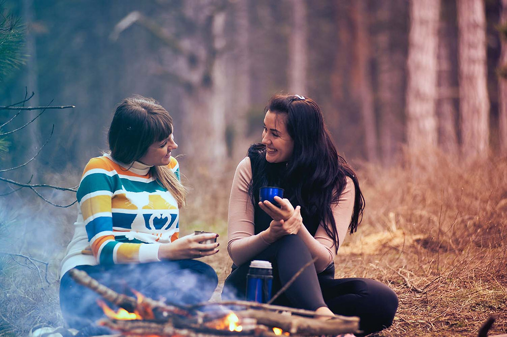 two girls talking and drinking near bonfire in nature