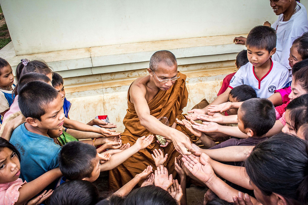 Children around buddhIst monk hold out their hands
