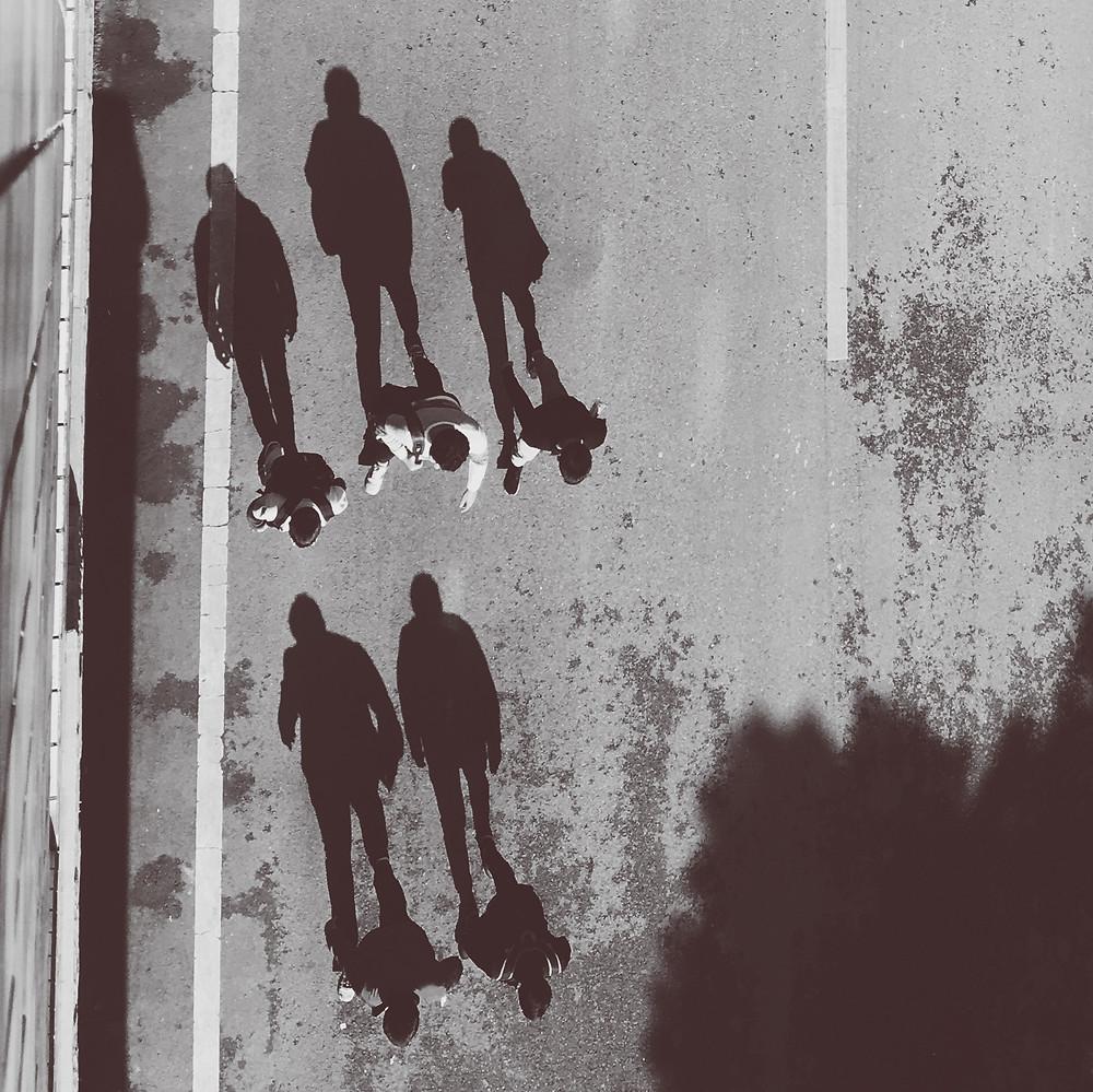 people walking shadows on road