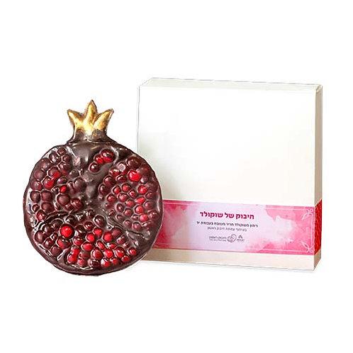 קופסה מרובעת לבנה עם פס בצבעי ורוד ושוקולד חלב בצורת רימון מעוטר בצע זהב ואדום