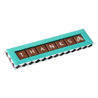 קופסה בצבע טורקיז ארוכה וצרה עם שבעה פרלינים משוקולד חלב עם כיתוב בצבע לבן של תודה באנגלית
