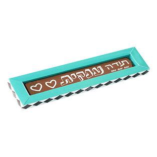 קופסה בצבע טורקיז ארוכה וצרה עם פרלין ארוך וצר משוקולד חלב ומעליו כיתוב בצבע לבן של תודה ענקית