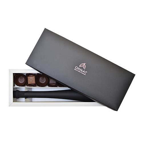 קופסה מלבנית לבנה עם מכסה שחור עם ליקר שוקולד גדול, פרלינים וספלונים משוקולד