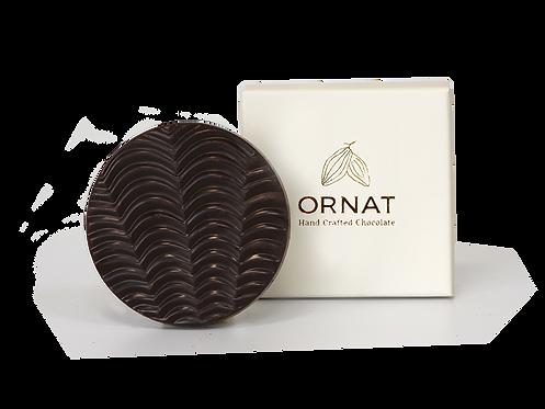 קופסה לבנה קטנה עם כיתוב לוגו החברה בצבע לבן  ודסקית עגולה משוקולד מריר עם חזית בצורת גלים